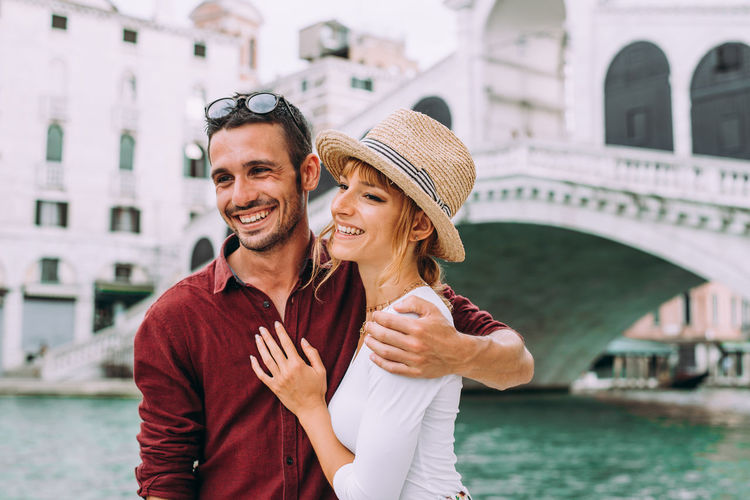 Smiling young couple embracing while standing against building in city