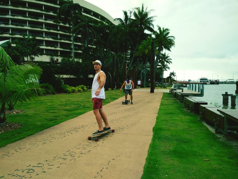 This is so awesome photography of two men riding skateboards on the pathway. Beautiful Photography💕 People Watching Me People Around  Skateboarding Life Pathway To Paradise People And Nature All Green 🌴☁🌲 Boats⛵️ Oceanfront People Having Fun Palm Trees Accommodation For Travellers Beautiful Nature The Following