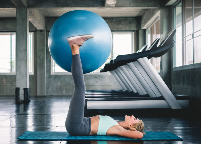 Full length of young woman exercising on mat at gym