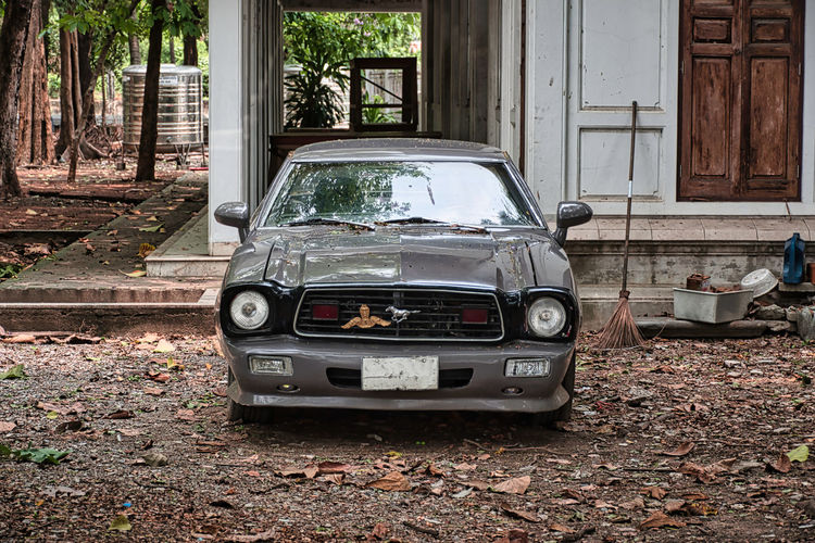 Abandoned car parked outside building