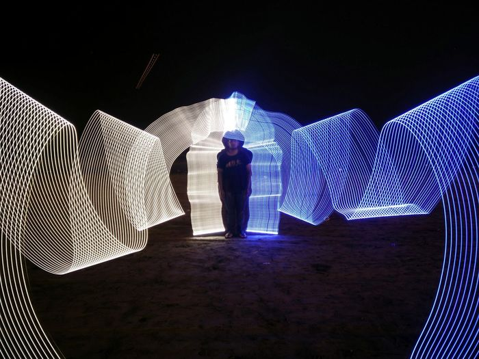 Young man standing amidst light painting on field at night