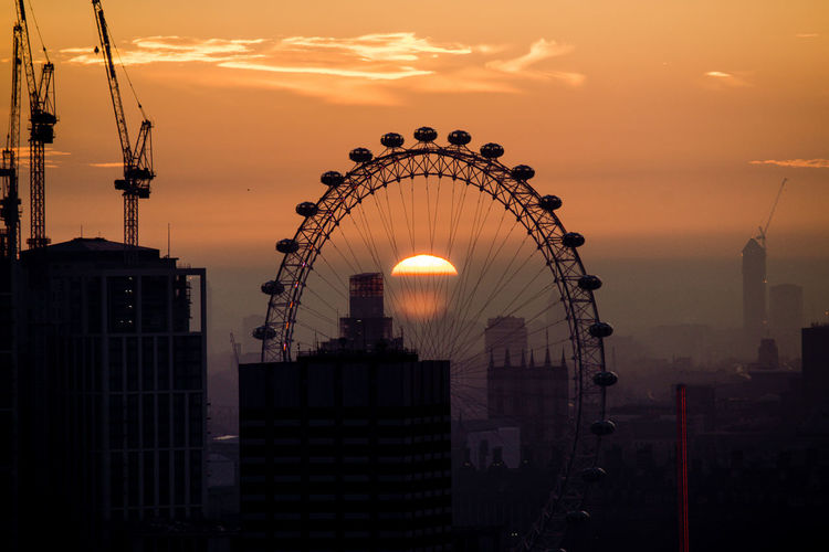 Silhouette Ferris Wheel Against Sky In City During Sunset