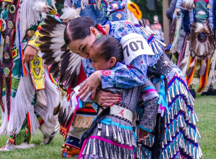 september 3, 2017, American Indian woman in traditional clothing, or reglaia,hugs her little girl during a competition at the Kee-Boon-Mein-Kaa Pow Wow in Dowagiac Michigan USA American Indians Native American Indian Adult Celebration Child Childhood Clothing Colorfulbeads Competition Culture Daughter Decorative Editorial  Emotion Family Girls Group Of People Native American People Positive Emotion Real People Regalia Togetherness Traditional Clothing Women