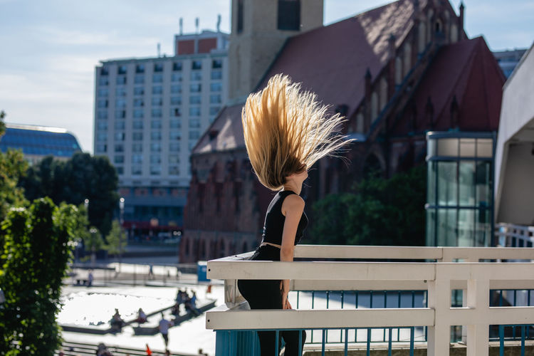 Side view of playful young woman tossing hair on balcony against buildings in city