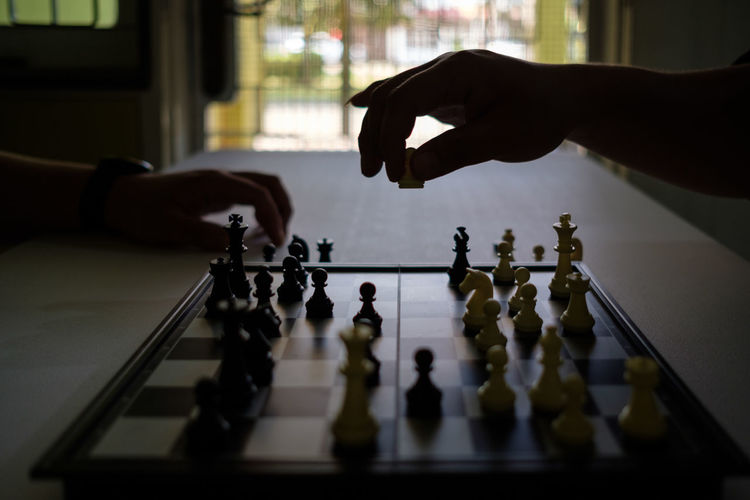 Cropped hands of people playing chess at home