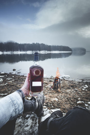 Fashion human hand holding a bottle of whiskey near a campfire Water Nature Sky Day Leisure Activity Men Holding Land Cloud - Sky People Real People Beach Lifestyles Photography Themes Scenics - Nature Sea Two People Tranquility Outdoors Hand Human Hand Bottle Alchohol Whiskey Campfire