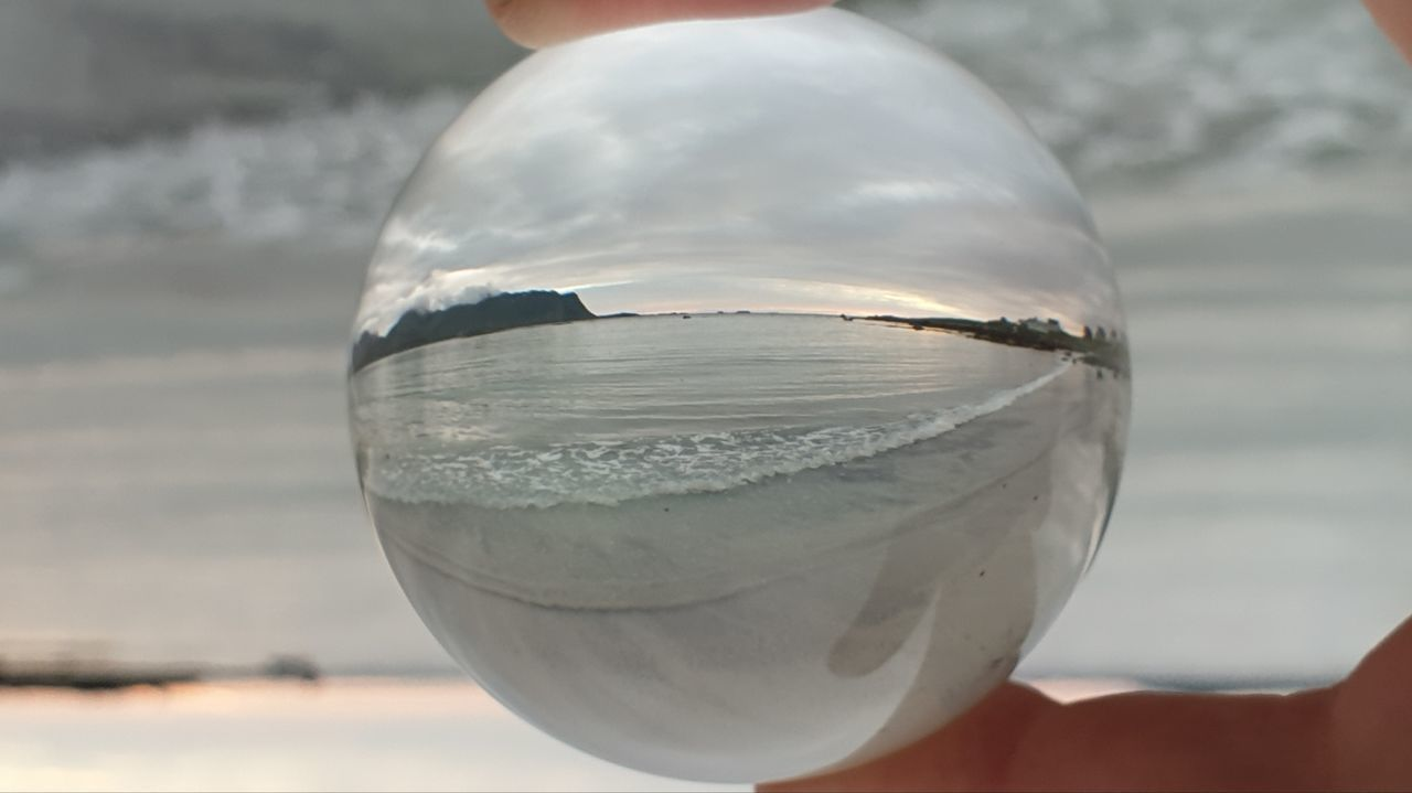 CLOSE-UP OF HAND HOLDING CRYSTAL BALL AGAINST GLASS