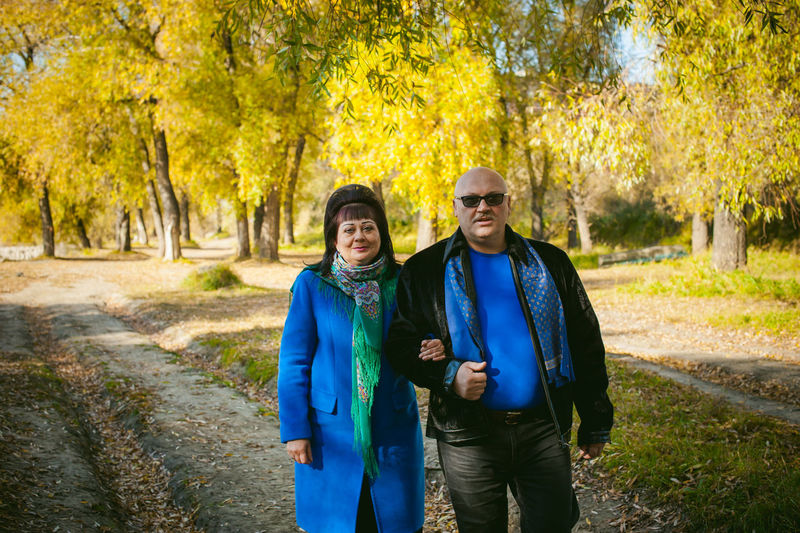 Portrait of mature couple walking in forest during autumn