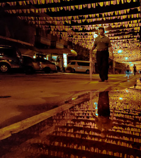 Rear view of man standing on illuminated street at night