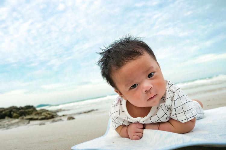 Portrait of cute boy at beach against sky