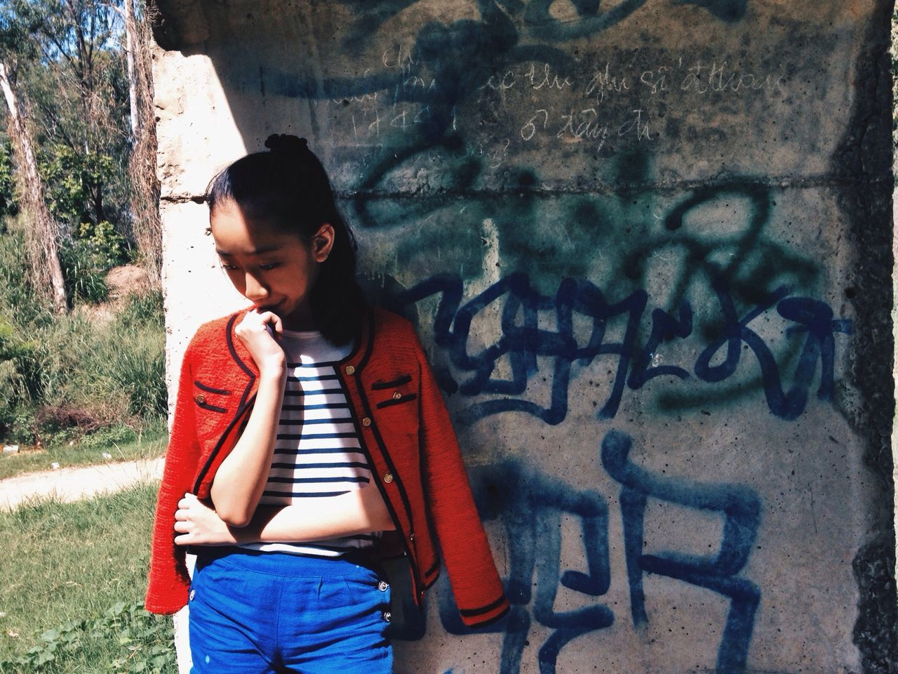 Thoughtful teenager with jacket standing against graffiti wall