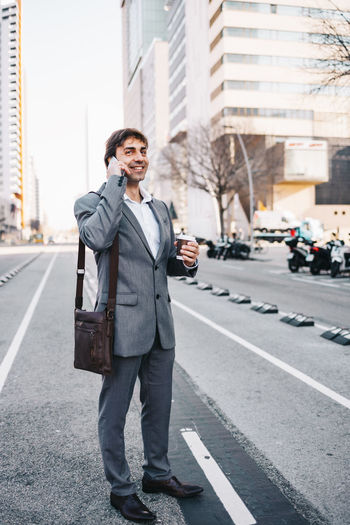 Full length of businessman talking on phone while standing on road
