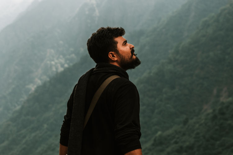 Side view of young man looking away against mountain