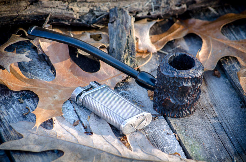 a rusticated setter pipe also called a popeye pipe, with a old silver flint lighter on a rustic outdoor background Objects Retro Tobacco Tobacco Pipe Briar Closeup Collection Craftsmanship  Ebonite Enjoyment Flint Lighter Habit Hand Made Handiwork Lifestyles Nicotine Old Outdoors Pipe Popeye Pipe Sitter Pipe Smoking Pipe Still Life Vintage Vulconite