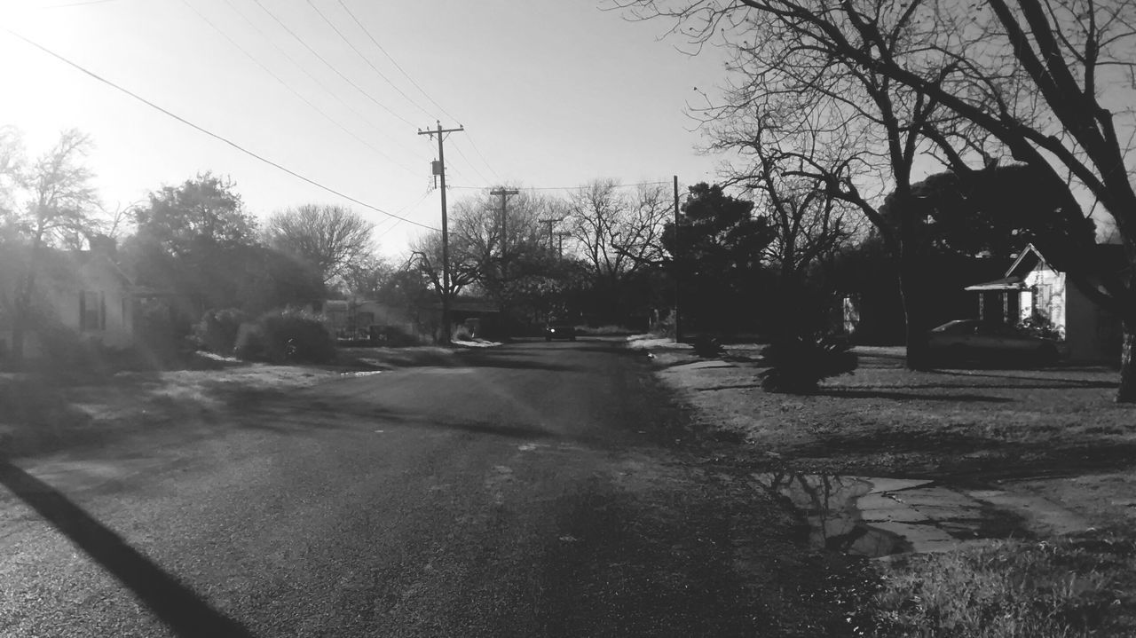 car, tree, transportation, land vehicle, road, cable, street, electricity, day, outdoors, electricity pylon, nature, bare tree, no people, sky, city