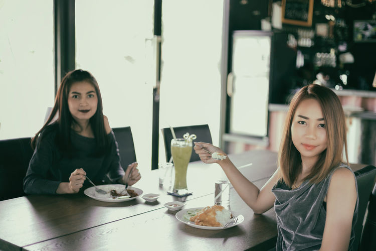 Portrait Of Smiling Young Women Sitting At Table In Restaurant