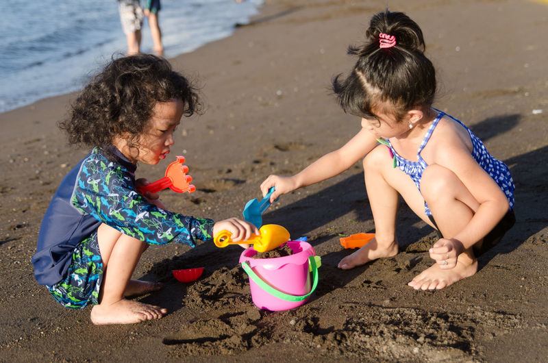Girl with sister playing with toys at beach