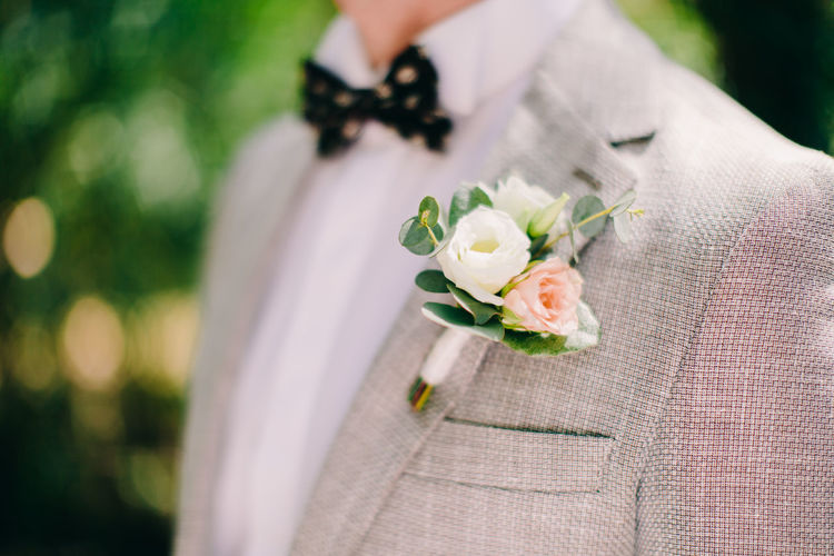 Midsection Of Bridegroom Wearing Boutonniere On Suit