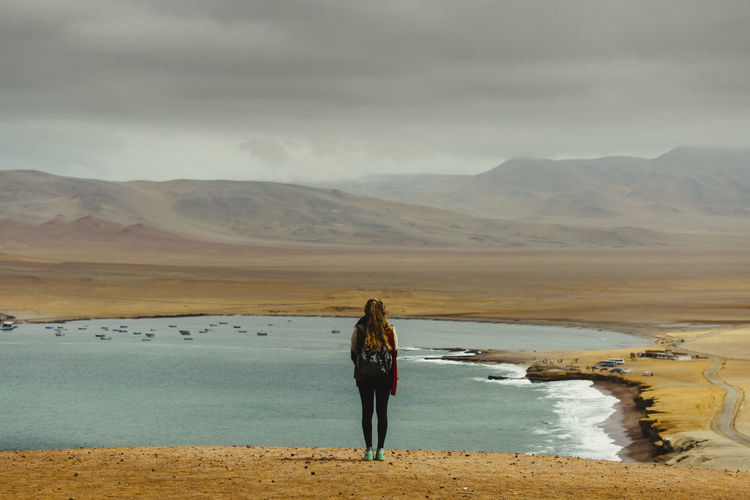 Rear view of woman looking at lake against cloudy sky