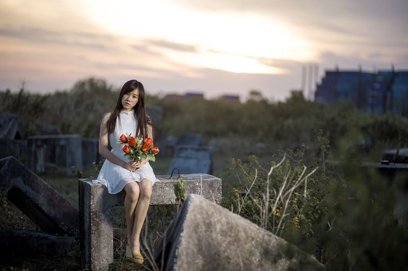 Portrait of young woman with flowers sitting on retaining wall against cloudy sky during sunset