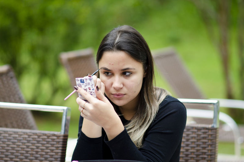 Portrait of young woman holding camera outdoors