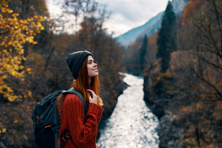 Young woman looking away while standing on land during autumn