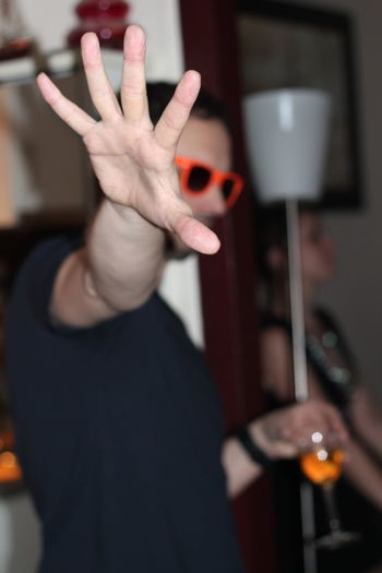 Young man gesturing stop sign at party