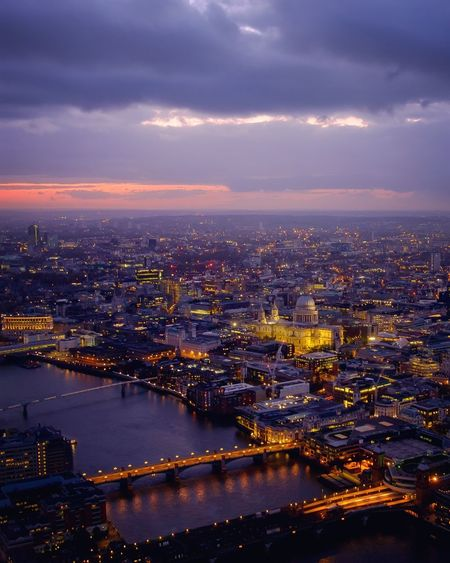 Aerial View Of Illuminated Buildings And Thames River Against Cloudy Sky At Dusk