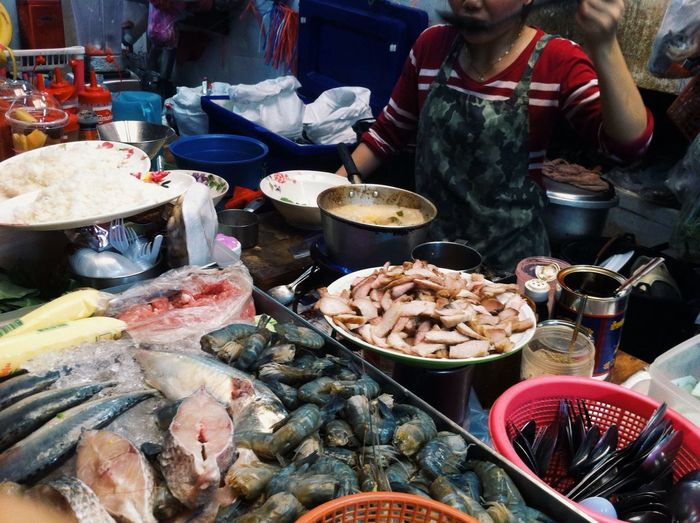 Midsection Of Woman Cooking Food In Street Market Stall