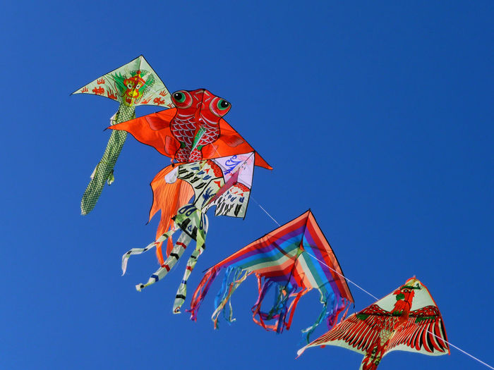 Low angle view of colorful kites against clear sky