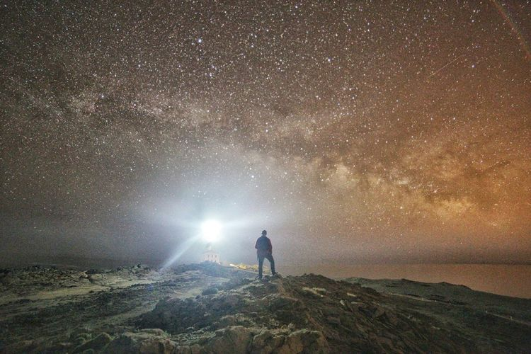 Rear view of man standing against glittering sky at night