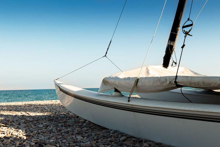 Sailboat moored on beach against clear sky
