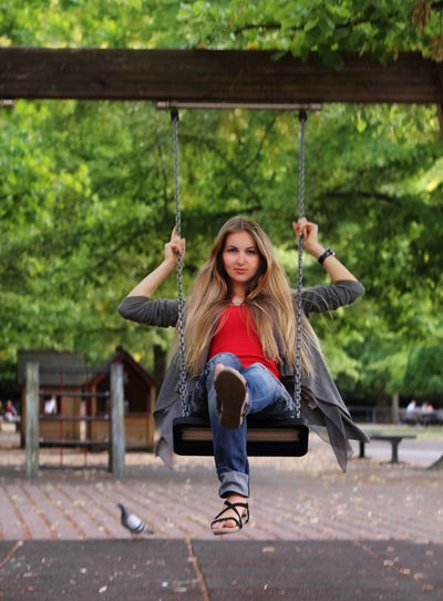 Portrait of smiling girl on swing at playground