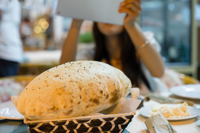 With a pad a girl is taking photo of a piece of Lavas, or Puff Bread, freshly served as dinner at Selcuk, Turkey. Bread Delicious Dinner Food Fresh Girl Night Pad Photographing Pitta Puff Restaurant Selective Color Tablet Taking Photos Tourist Tradition Travel Turkey