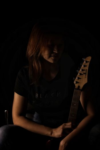 Woman with a guitar in darkroom
