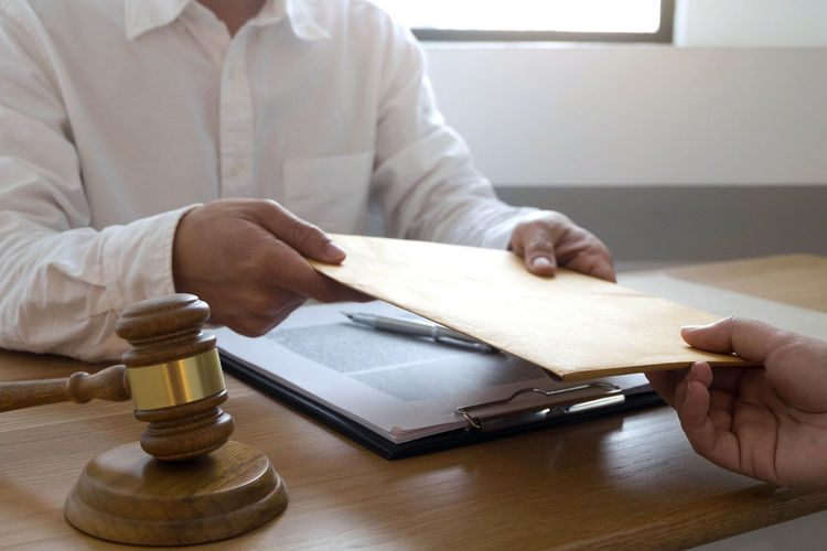 Midsection of lawyer with client holding envelope over office desk