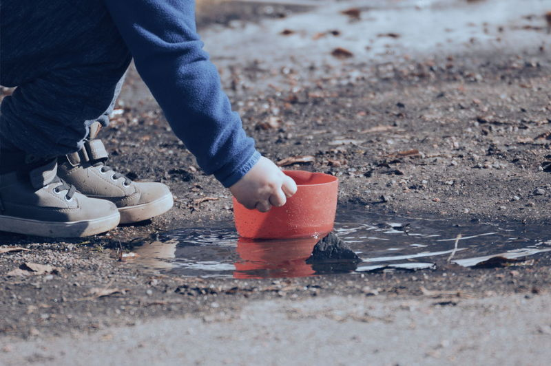 Low section of child holding container on puddle