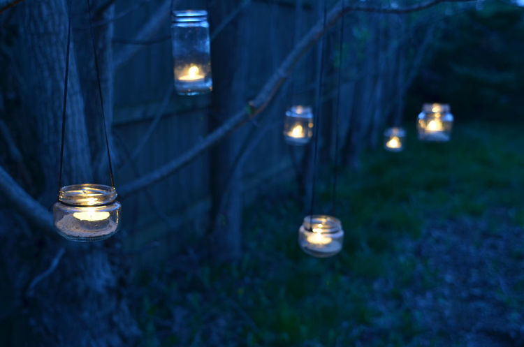 night scene with homemade hand-crafted lanterns made from small glass jars with tea light candles inside tied to tree branches Burning Candle Candles Close-up Flame Glowing Hanging Illuminated Iluminated In A Row Jars  Lantern Lanterns Night No People Outdoors Tea Light Tea Lights