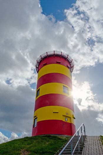 Low angle view of multi colored lighthouse against sky