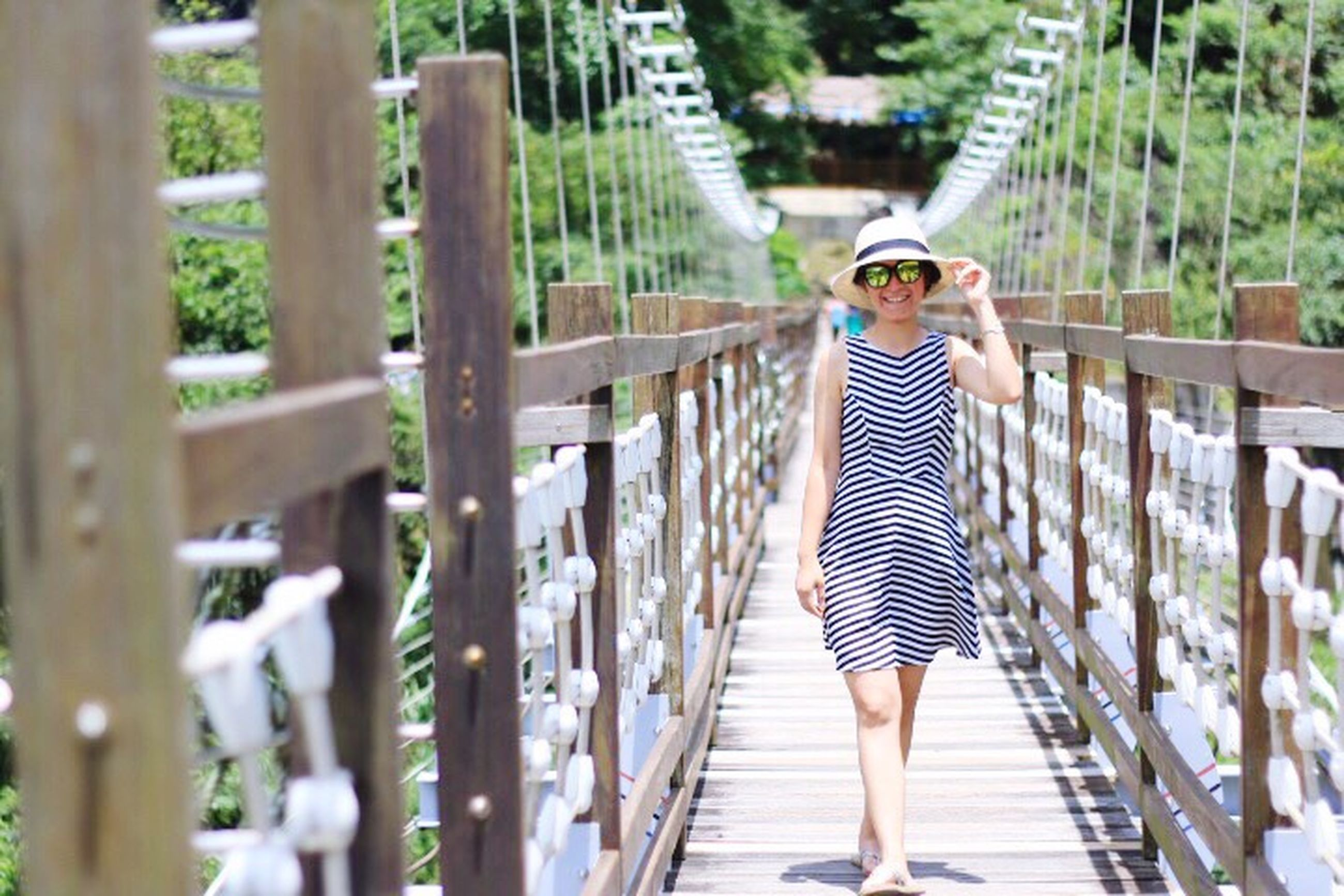 striped, one person, young adult, full length, casual clothing, young women, one woman only, railing, only women, adults only, adult, leisure activity, standing, real people, outdoors, beautiful woman, bridge - man made structure, day, women, vacations, one young woman only, people, lifestyles, footbridge, beautiful people, smiling, portrait, beauty in nature, nature