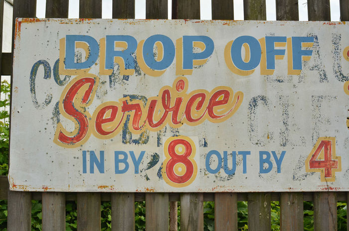 hand-painted lettering in red, yellow, and blue overtop ghostghost sign Close-up Communication Day Ghost Signs  Hand Lettering Hand Painted Sign No People Outdoors Retro Style Signboard Text Western Script