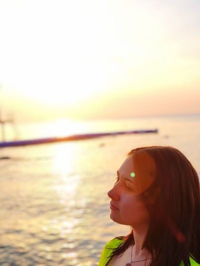 Water Sea Real People One Person Sky Leisure Activity Lifestyles Beauty In Nature Women Young Women Nature Land Beach Sunset Headshot Young Adult Sunlight Focus On Foreground Outdoors Horizon Over Water