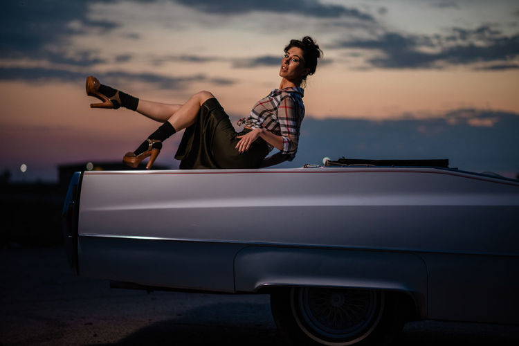 Portrait of woman standing by car against sky during sunset