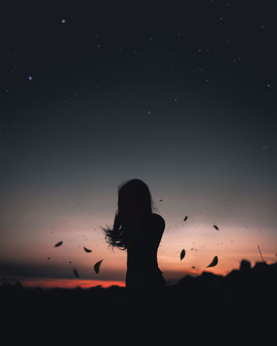 Girl silhouette with falling leaves during sunset Sky Real People One Person Lifestyles Sunset Standing Nature Women Girl Window Leaves Leaves Falling Stars Night Sky Silhouette