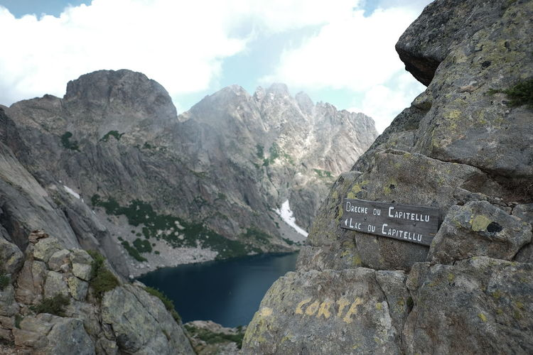 Path to Capitello Lake Beauty In Nature Communication Day Eroded Formation Lake Mountain Mountain Peak Mountain Range Nature No People Non-urban Scene Outdoors Rock Rock - Object Rock Formation Scenics - Nature Sign Sky Solid Text Tranquil Scene Tranquility Water Western Script
