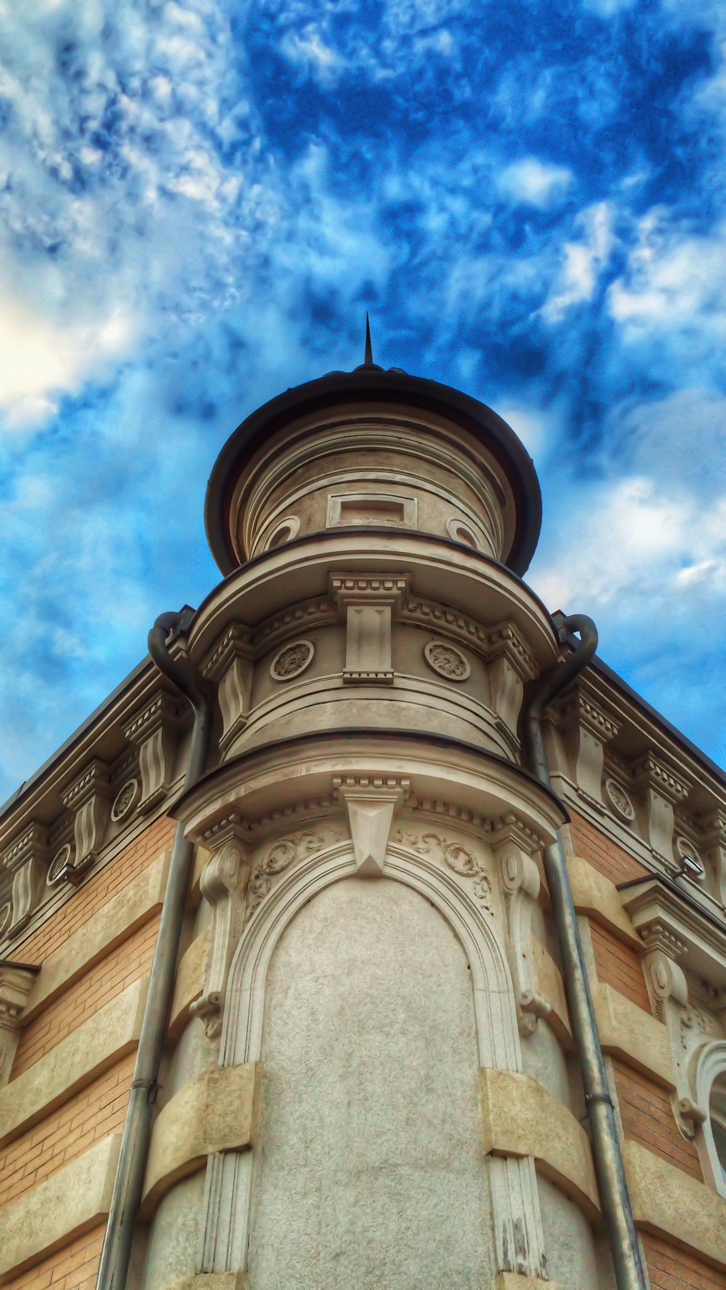 architecture, low angle view, building exterior, built structure, sky, cloud - sky, cloud, church, religion, cloudy, history, arch, place of worship, outdoors, day, high section, no people, city, travel destinations