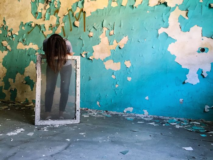 Woman Bending Against Weathered Wall In Abandoned Room
