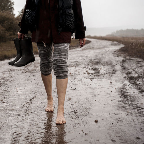 Low section of man walking on wet sand