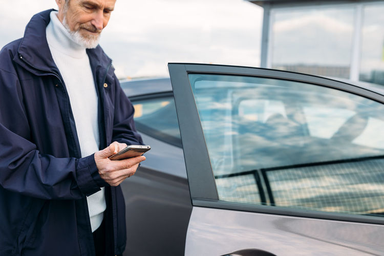Man using mobile phone while standing by car