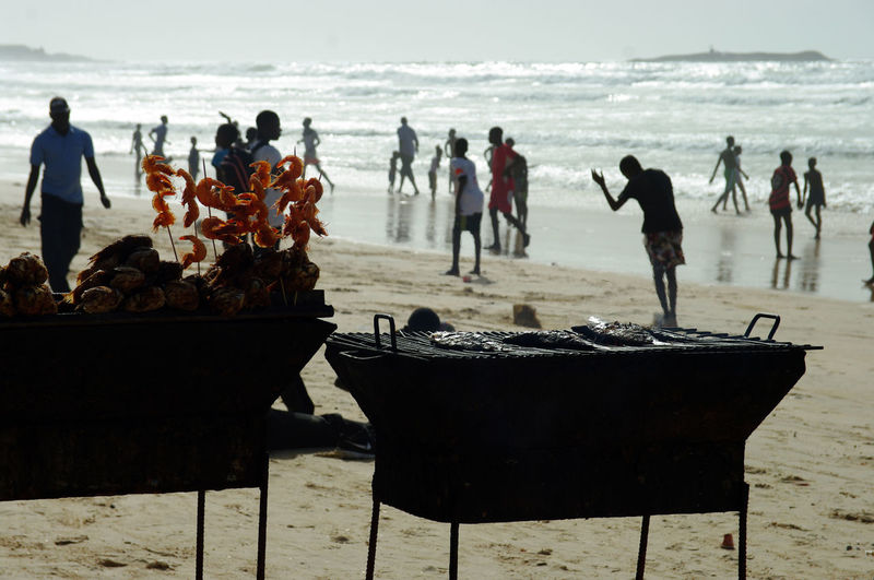 People by barbecue at beach
